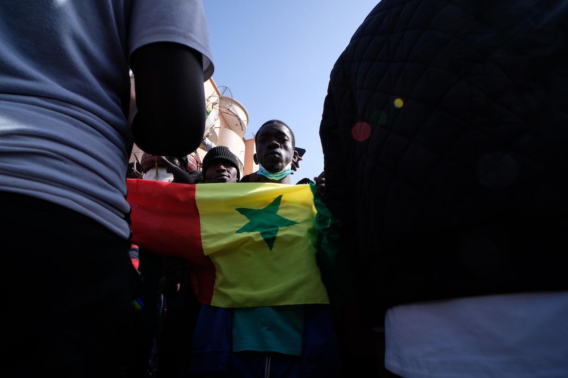 Senegal, un manifestante tiene in mano la bandiera del Paese