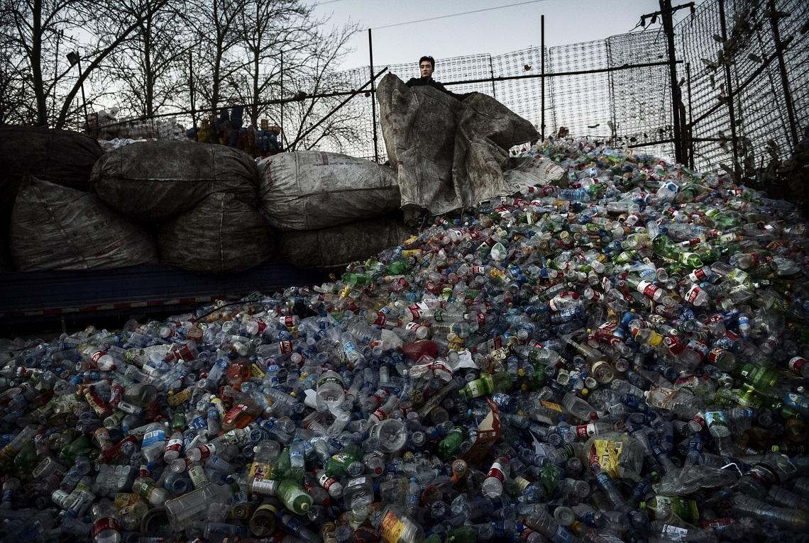 Un lavoratore cinese scarica le bottiglie di plastica da riciclare