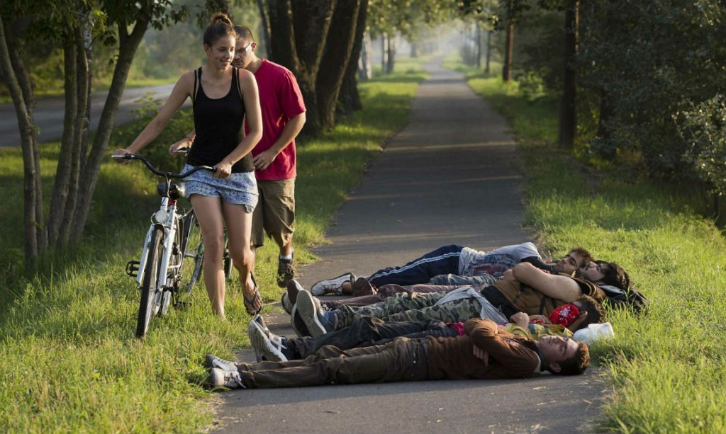 Europe-Refugee-Crisis-Local-cyclists-pass-a-group-of-refugees-sleeping-on-a-bicycle-path