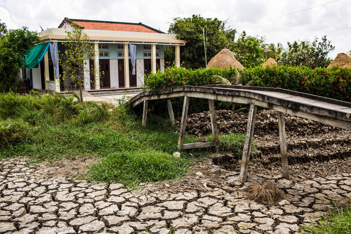 BEN TRE PROVINCE, VIETNAM - MAY 04: A bridge leeds over a dried out fish pond on May 04, 2016 in Ben Tre Province, Vietnam.  Vietnam's Mekong Delta had been hit by its worst drought in 90 years caused by the El Nino weather patterns and hydroelectric dams. Based on reports, nearly 140,000 hectares of the Mekong Delta in Vietnam are bone dry and contaminated by salt water, as brine from the sea pushes up the delta's channels. People in affected regions are growing desperate to find water for basic needs and huge amount of the crops for the coming harvest in Vietnam's Mekong Delta, which produces about half of the country's rice, have been spoiled.   (Photo by Christian Berg/Getty Images)
