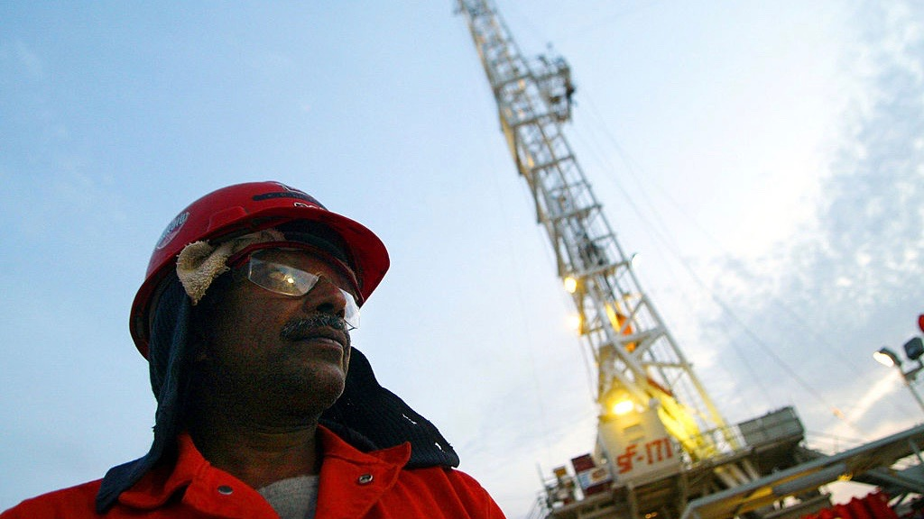 An oil worker walks past a ChevronTexaco drilling platform near the Saudi Arabian border © Joe Raedle/Getty Images
