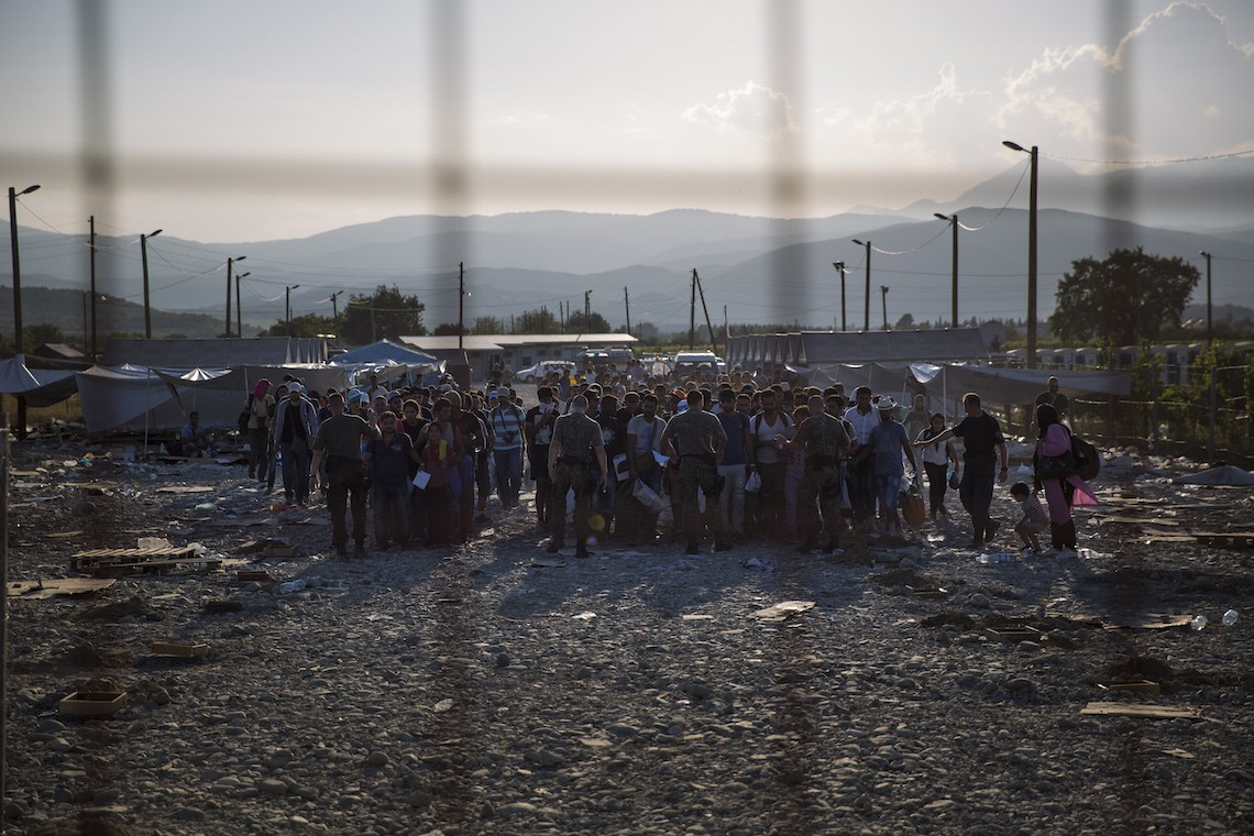 GEVGELIJA, MACEDONIA - SEPTEMBER 03: After crossing the Greek Macedonian border and having papers processed, migrant families prepare to walk out of a transit area towards Gevgelija train station to find transport North to the Serbian border on September 3, 2015 near Gevgelija, Macedonia. Since the beginning of 2015 the number of migrants using the so-called 'Balkans route' has exploded with migrants arriving in Greece from Turkey and then travelling on through Macedonia and Serbia before entering the EU via Hungary. The number of people leaving their homes in war torn countries such as Syria, marks the largest migration of people since World War II. (Photo by Dan Kitwood/Getty Images)