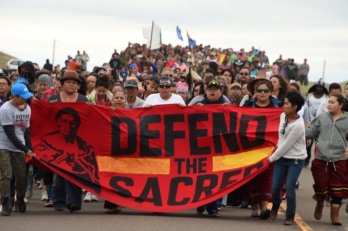 "Nativi americani marciano con il cartellone ""Defend the sacred"" contro la costruzione dell'oleodotto Dakota access pipeline (DAPL) in Nord Dakota."