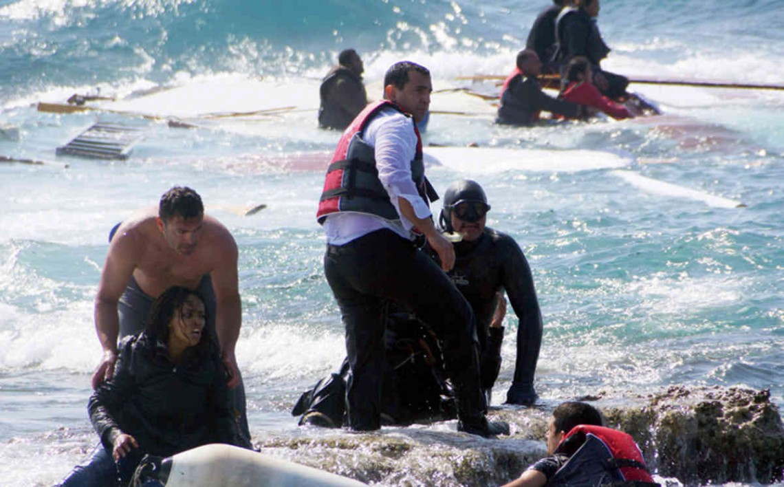 A man rescues an migrant from the Aegean sea, in the eastern island of Rhodes, Monday, April 20, 2015. Greek authorities said that at least three people have died, including a child, after a wooden boat carrying tens of migrants ran aground off the island of Rhodes. (Argiris Mantikos/Eurokinissi via AP) GREECE OUT