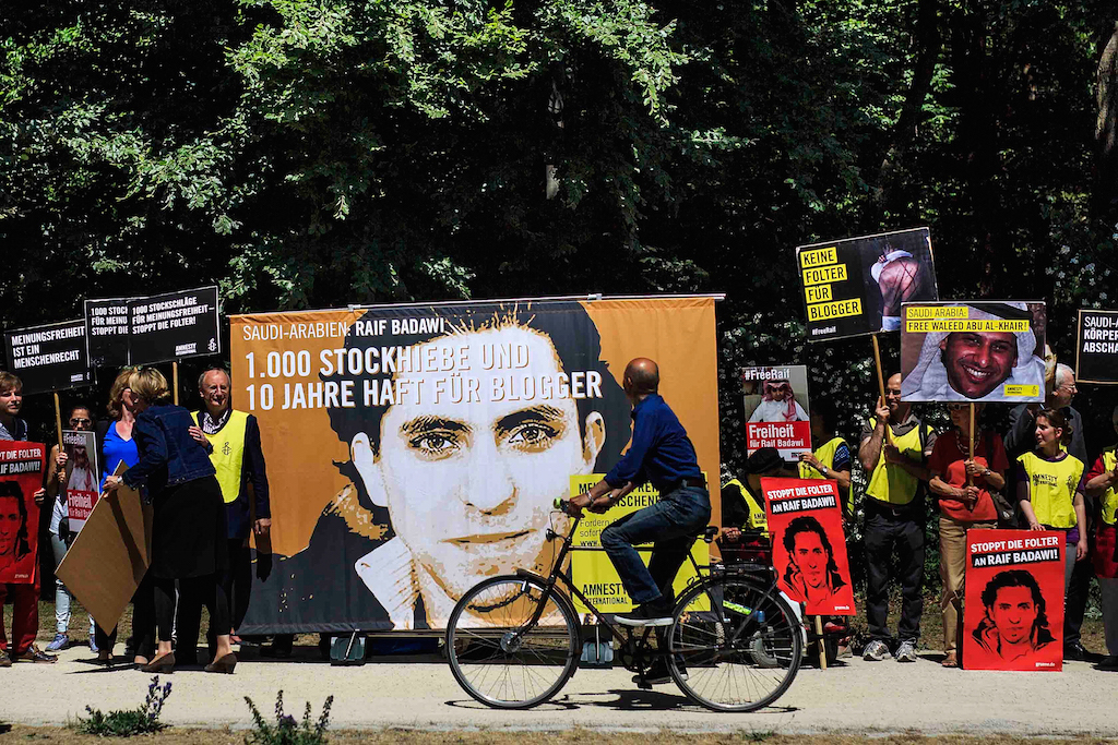 BERLIN, GERMANY - JUNE 11:  A cyclist passes as activists demonstrate outside the Saudi Arabian Embassy against the recent Saudi court ruling that upheld a previous verdict of ten years in prison and 1,000 lashes for Saudi blogger Raif Badawi on June 11, 2015 in Berlin, Germany. The court accuses Badawi of insulting Islam in an Internet forum. (Photo by Carsten Koall/Getty Images)