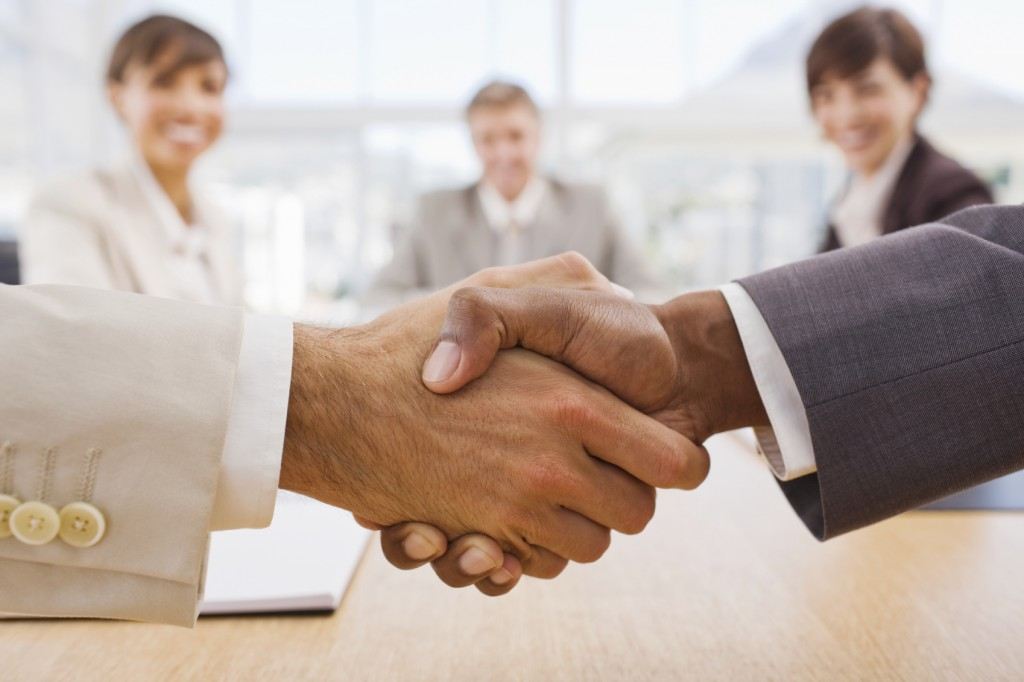 Portrait of happy businesspeople shaking hands
