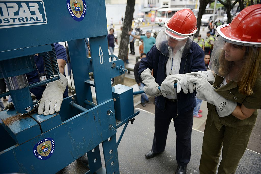 Police destroy handguns by means of an industrial press during a weapon destruction operation in Caracas on May 20, 2013. AFP PHOTO/Leo RAMIREZ        (Photo credit should read LEO RAMIREZ/AFP/Getty Images)